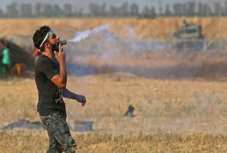 A Palestinian protester holds a tear gas canister in his mouth during a demonstration along the border with Israel east of Khan Yunis in the southern Gaza strip