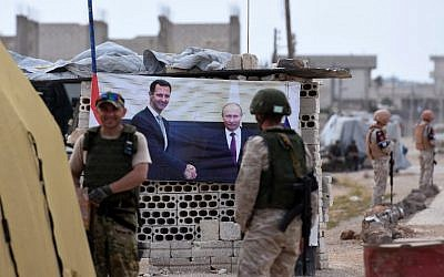 Members of the Russian military stand past a banner showing Russian President Vladimir Putin, right, shaking hands with Syrian President Bashar Assad, at Abu al-Zuhur checkpoint in the western countryside of Idlib province on June 1, 2018. (AFP PHOTO / George OURFALIAN)