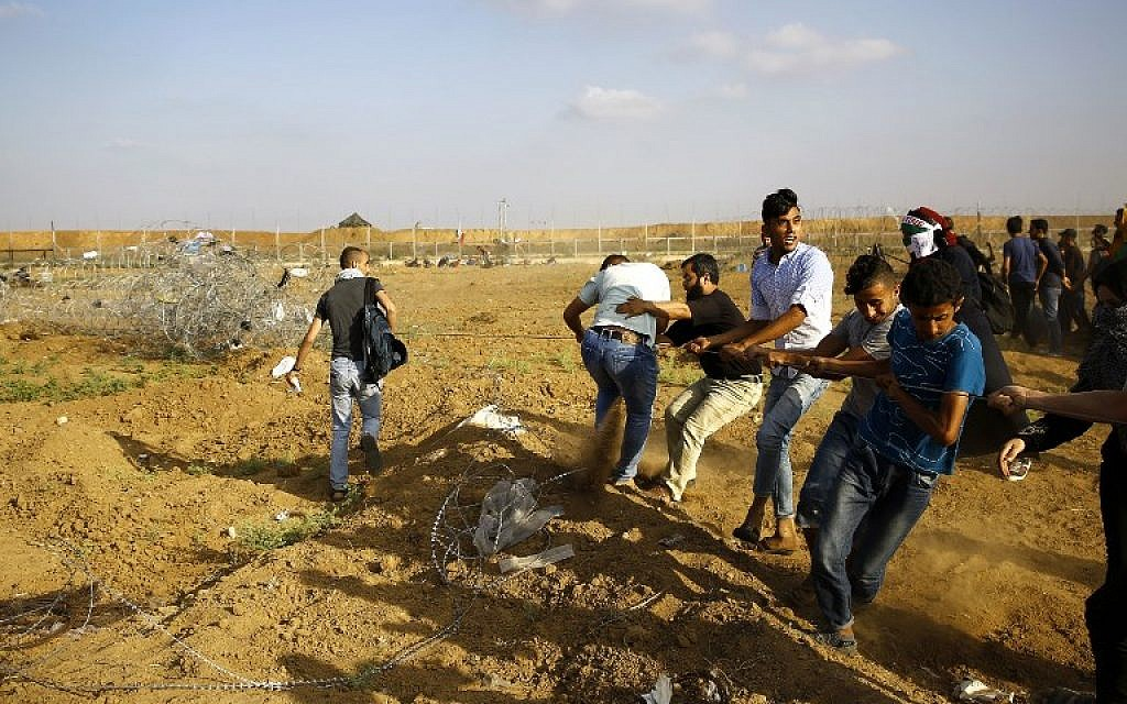 Palestinans pull a metal cable as they try to take down a section of barbed wire on the border fence with Israel, east of Jabaliya in the central Gaza Strip, on June 1, 2018.(AFP Photo/Mohammed Abed)