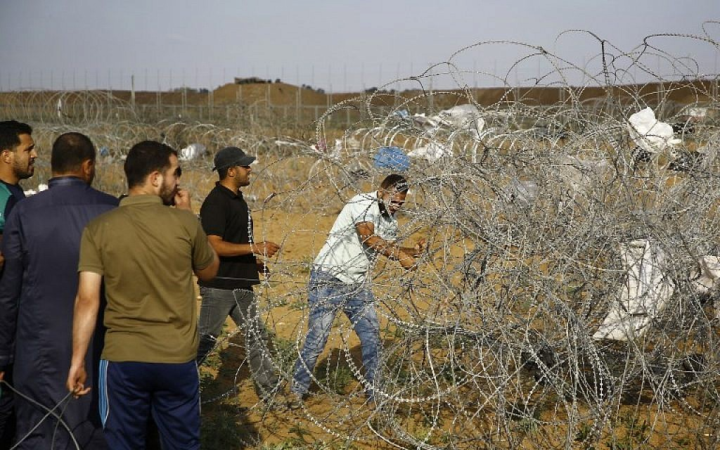 A Palestinan protester cuts a section of barbed wire on the border fence with Israel, east of Jabalia in the central Gaza Strip on June 1, 2018. (AFP PHOTO / Mohammed ABED)