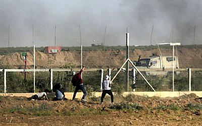 A Palestinian man throws a stone toward Israeli forcesduring a demonstration along the Gaza border on June 1, 2018. (AFP/ Mahmud Hams)