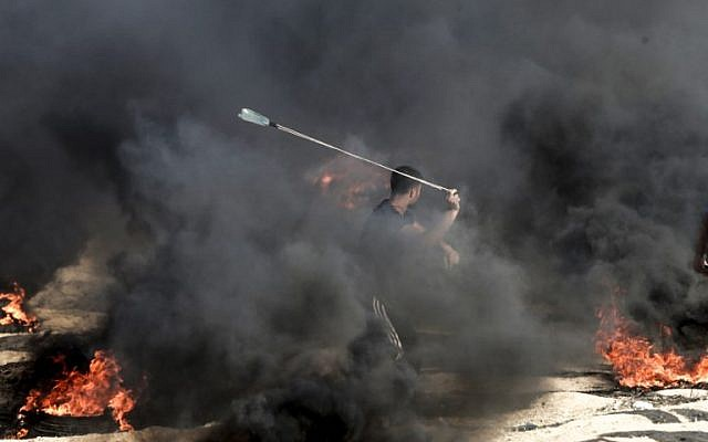 A Palestinian protester uses a slingshot to throw a stone towards Israeli forces as smoke billows from burning tires during a demonstration along the border with the Gaza strip east of Gaza city on June 1, 2018.  (AFP PHOTO / Mahmud Hams)