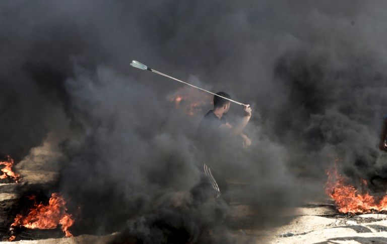 A Palestinian protester uses a slingshot to throw a stone towards Israeli forces as smoke billows from burning tires during a demonstration along the border with the Gaza strip east of Gaza city