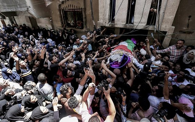 Palestinian mourners carry the body of  21-year-old Palestinian paramedic Razan al-Najjar at her funeral in Khan Yunis on June 2, 2018. (AFP/Mahmud Hams)