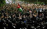 Members of the Jordanian gendarmerie and security forces stand on alert as protesters shout slogans and raise a national flag during a demonstration outside the Prime Minister's office in the capital Amman late on June 2, 2018. (AFP PHOTO / Khalil MAZRAAWI)