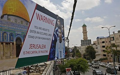 A picture taken on June 5, 2018, shows a poster erected on a main street in the West Bank town of Hebron, denouncing the upcoming friendly football match between Argentina and Israel and calling Argentina's star Lionel Messi (portrait) to boycott the match. (AFP PHOTO / HAZEM BADER)