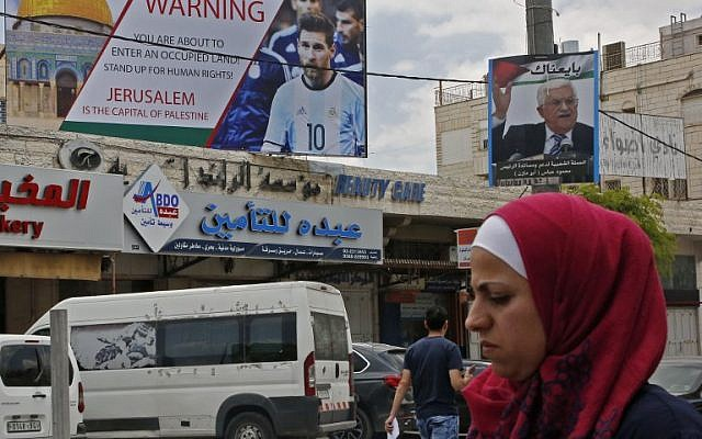 This June 5, 2018, picture shows a poster erected in the West Bank town of Hebron calling for a boycott of soccer star Lionel Messi (l) next to a portrait of the Palestinian Authority President Mahmoud Abbas. (AFP PHOTO / HAZEM BADER)