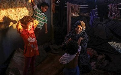 Noor, the 33-year-old wife of Hani al-Laham, an employee of the Ramallah-based Palestinian Authority government, sits with her children in their shack home near the beach in Gaza City on June 4, 2018. (AFP Photo/Mohammed Abed)