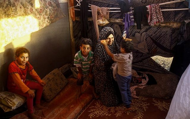 A woman sits with her children in their shack home near the beach in Gaza City on June 4, 2018. (MOHAMMED ABED/AFP)