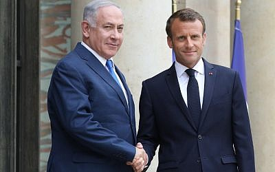 French President Emmanuel Macron shakes hands with Prime Minister Benjamin Netanyahu (L) at the Elysee Palace in Paris on June 5, 2018. (AFP/Ludovic Marin)