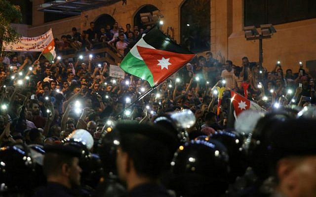 Demonstrators wave Jordanian flags and hold up their lit mobile phones as they face Jordanian police officers during a protest near the prime minister's office in Amman, Jordan, on June 5, 2018. (AFP/Khalil Mazraawi)