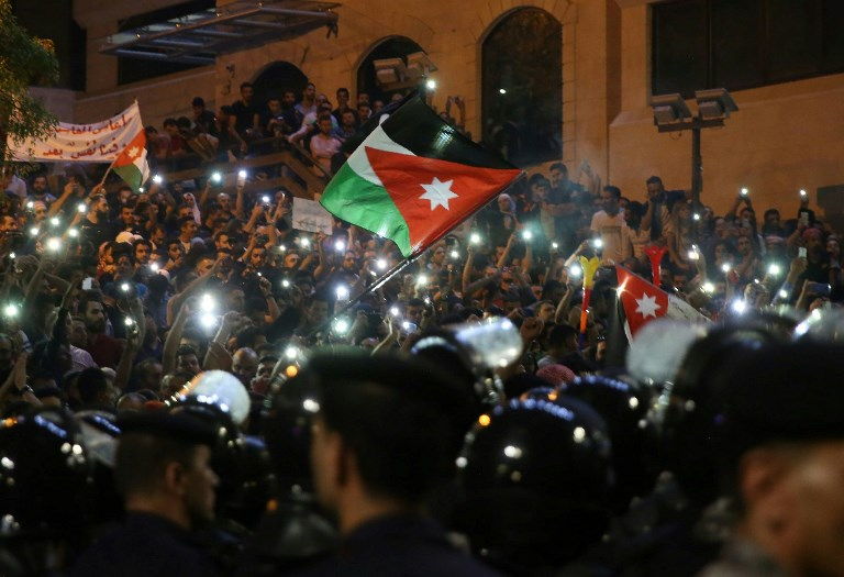 837e1cefc58bf2 Demonstrators wave Jordanian flags and hold up their lit mobile phones as  they face Jordanian police