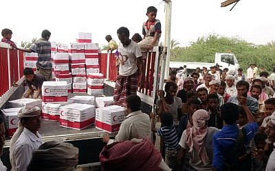 Yemenis drop off boxes of humanitarian aid provided by the Emirati Red Crescent in the coastal town of Mujailis, south of the city of Hodeida, on June 6, 2018. (AFP PHOTO / NABIL HASSAN)