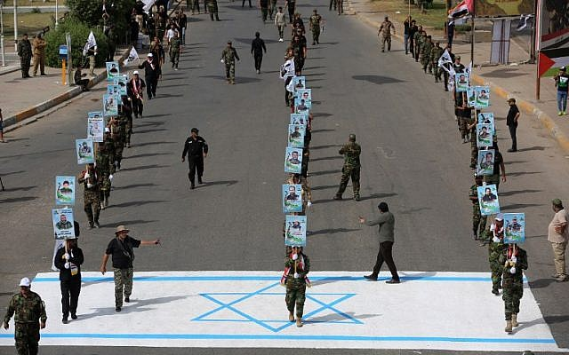 "Iran-allied Shiite paramilitary fighters step on an Israeli flag drawn on the pavement during a rally to mark ""Quds Day"" (Jerusalem Day) first initiated by Iran in 1979 to fall on the last Friday of the holy month of Ramadan, in the Iraqi capital Baghdad on June 8, 2018. (AFP Photo/Ahmad al-Rubaye)"