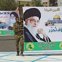Shiite militiamen carry a poster of Iran's supreme leader, Ayatollah Ali Khamenei, while stepping on a drawing of an Israeli flag during a Jerusalem Day rally in the Iraqi capital Baghdad, June 8, 2018. (AFP/Ahmad Al-Rubaye)
