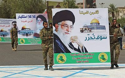 Shiite militiamen carry a poster of Iran's supreme leader, Ayatollah Ali Khamenei, while stepping on a drawing of an Israeli flag drawing, during a Jerusalem Day rally in the Iraqi capital Baghdad on June 8, 2018. (AFP Photo/Ahmad Al-Rubaye)