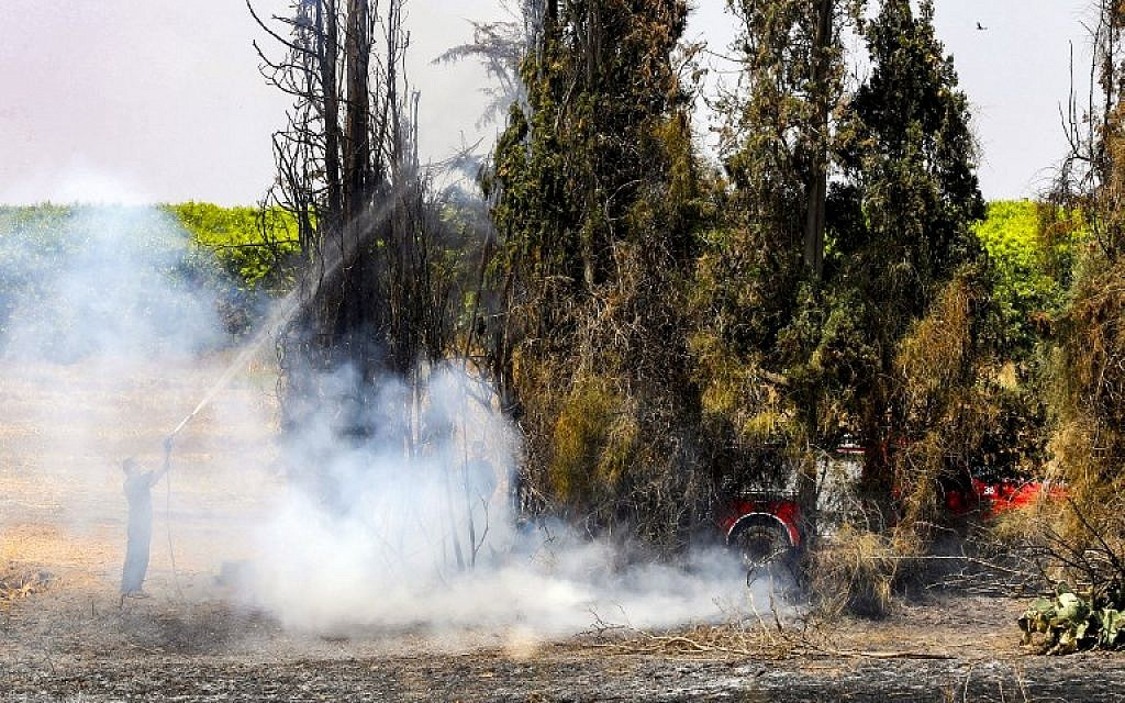 A firefighter attempts to extinguish a fire near Kibbutz Nahal Oz, along the border with the Gaza Strip on June 8, 2018, after it was sparked by a flaming kite flown by Palestinians from across the border. (AFP Photo/Jack Guez)