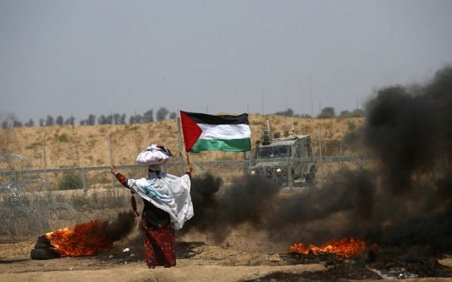 A woman stands holding a Palestinian flag with a cloth sack placed above her head before a barbed-wire fence and next to burning tires, during clashes following a demonstration near the border with Israel east of Khan Yunis in the southern Gaza Strip on June 8, 2018. (AFP/ SAID KHATIB)