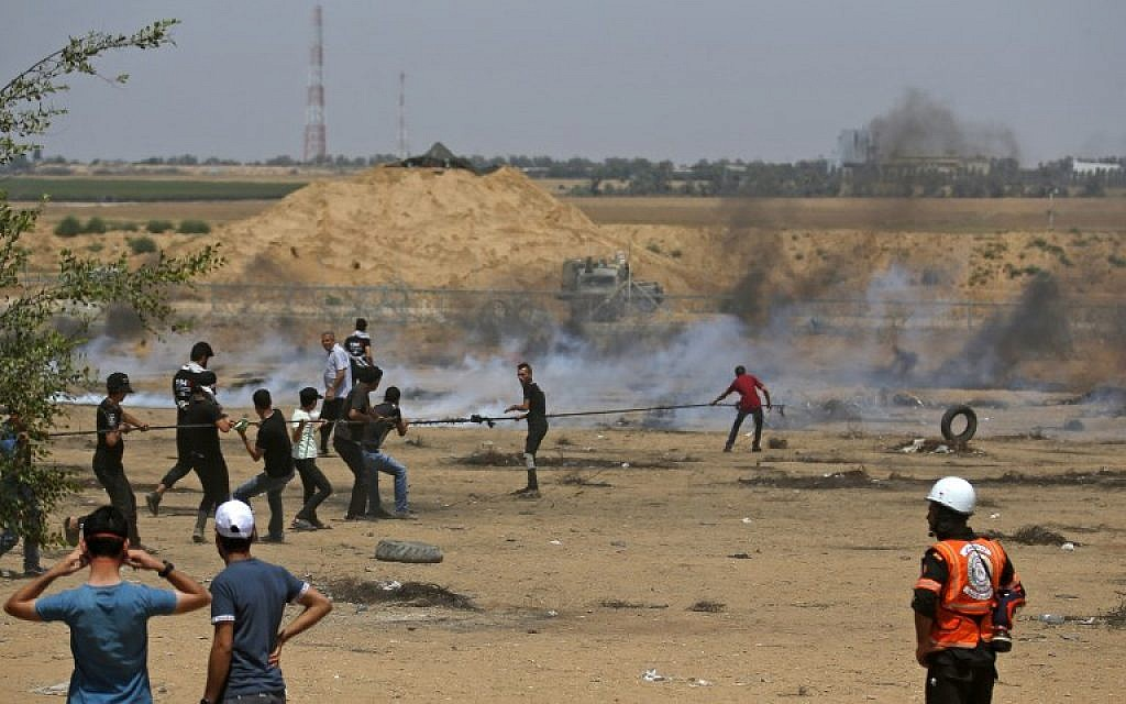 Palestinians pull on a cable tied to a barbed-wire fence as they try to pull down a section of the fence with Israel, during border clashes east of Khan Younis in the southern Gaza Strip, on June 8, 2018. (AFP Photo/Said Khatib)