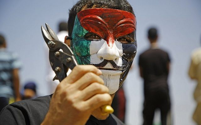 A Palestinian youth wearing a Guy Fawkes mask coloured with the Palestinian flag brandishes a pair of shears during a mass demonstration along the border fence east of Jabalia in the central Gaza Strip on June 8, 2018.(Mohammed Abed/AFP)