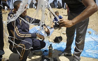 Palestinian protesters prepare an incendiary kite to be flown towards Israel on June 8, 2018 during a demonstration along the Israel-Gaza border fence east of Jabalia in the central Gaza Strip. (AFP/Mohammed Abed)
