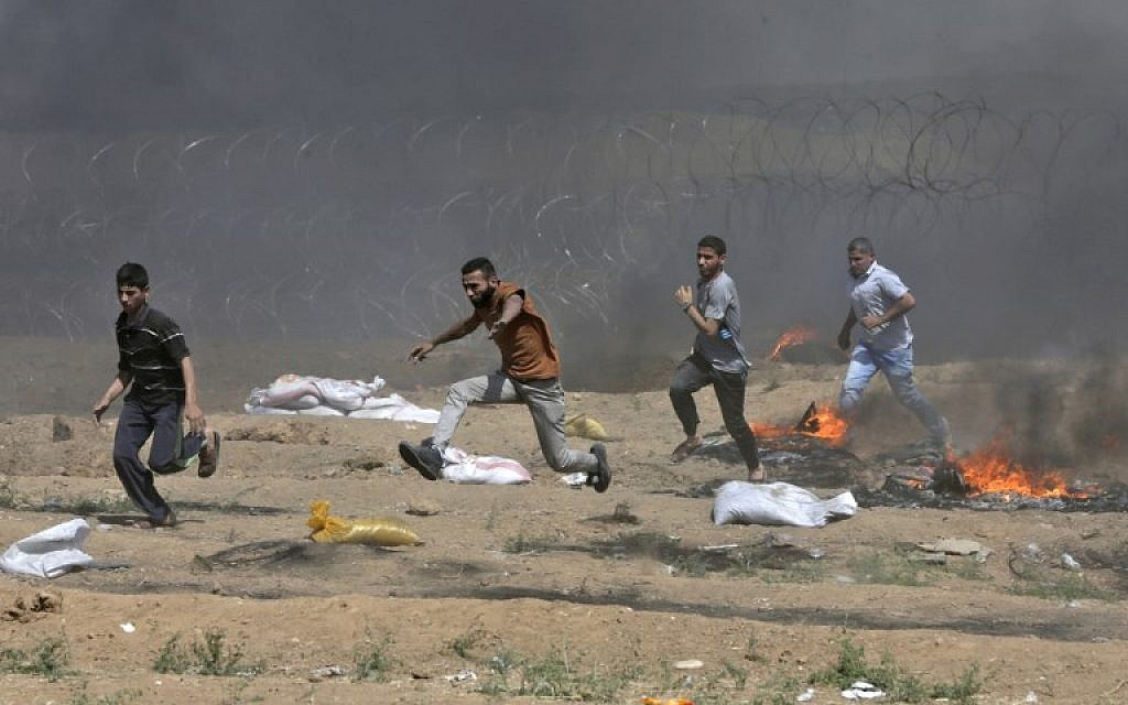 Illustrative. Palestinians run near the barbed-wire fence with Israel during clashes following a demonstration along the border with the Gaza Strip east of Gaza City on June 8, 2018. (AFP/Mahmud Hams)