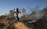 A Palestinian youth uses a slingshot to hurl stones at Israeli forces during clashes near the border with Israel, east of Khan Younis in the southern Gaza Strip on June 8, 2018. (Said Khatib/AFP)