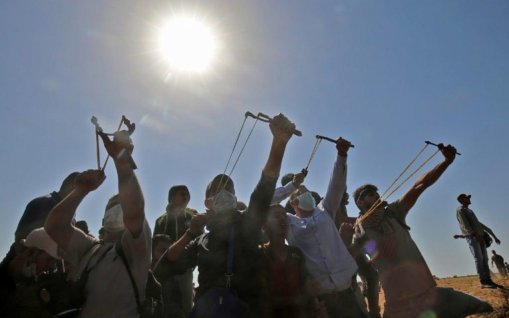 Palestinians use slingshots to hurl stones toward Israeli forces during clashes near the border with Israel, east of Khan Younis in the southern Gaza Strip, on June 8, 2018. (AFP Photo/Said Khatib)
