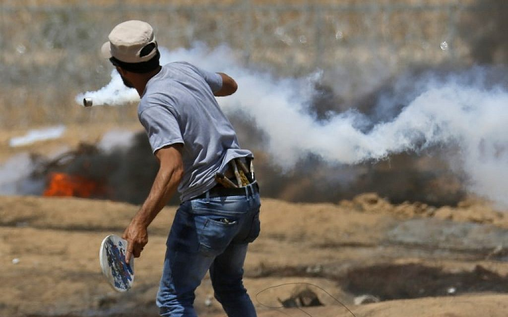 A Palestinian uses a wooden racket to hit back a tear gas canister during clashes with Israeli forces near the border with Israel, east of Khan Younis in the southern Gaza Strip, on June 8, 2018. (AFP Photo/Said Khatib)