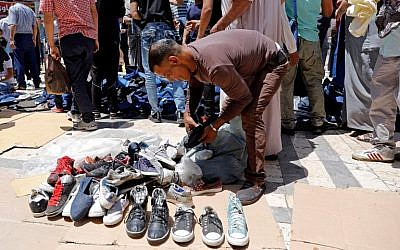 Jordanians buy second-hand shoes in an open air market in central Amman on June 8, 2018. (AFP Photo/Ahmad Gharabli)