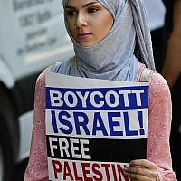 Illustrative: A protester holds a sign reading 'Boycott Israel, Free Palestine' during a Quds-day demonstration in Berlin, on June 9, 2018. (AFP PHOTO / Tobias SCHWARZ)