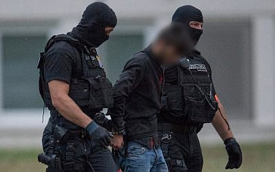 Police officers of a special unit escort Iraqi asylum seeker Ali Bashar, who is suspected of having killed a German teenage girl, from a helicopter to the police headquarters in Wiesbaden, western Germany, after he was flown back from Erbil to Germany on June 9, 2018. His face was blurred under German law( AFP PHOTO / dpa / Boris Roessler)