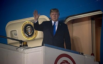 US President Donald Trump waves after Air Force One arrived at Paya Lebar Air Base in Singapore on June 10, 2018. (SAUL LOEB/AFP)