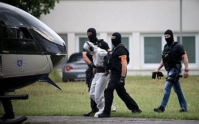 Police officers of a special unit escort Iraqi asylum seeker Ali Bashar, who is suspected of having killed a German teenage girl, to a helicopter in Wiesbaden, western Germany, on June 10, 2018, heading to a prison after Bashar testified. (AFP / dpa / Hasan BRATIC)