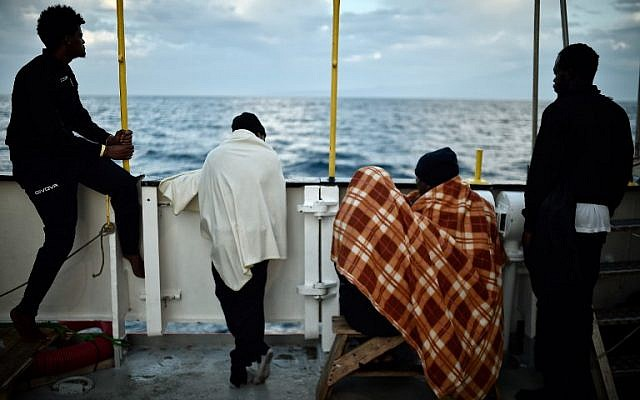 In this photo taken on May 14, 2018 migrants look at the coastline as they stand aboard the French rescue ship MV Aquarius, off the coast of Sicily. (AFP PHOTO / LOUISA GOULIAMAKI)