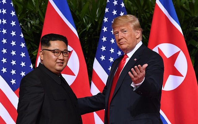 US President Donald Trump (R) gestures as he meets with North Korea's leader Kim Jong Un (L) at the start of their historic US-North Korea summit, at the Capella Hotel on Sentosa island in Singapore on June 12, 2018. ( AFP PHOTO / SAUL LOEB)