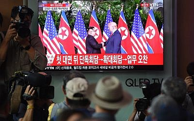 People watch a television screen showing live footage of the summit between US President Donald Trump and North Korean leader Kim Jong Un in Singapore, at a railway station in Seoul on June 12, 2018. ( AFP PHOTO / Jung Yeon-je)