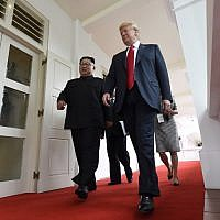 North Korea's leader Kim Jong Un (L) walks with US President Donald Trump (R) at the start of their historic US-North Korea summit, at the Capella Hotel on Sentosa island in Singapore, on June 12, 2018. (AFP Photo/Saul Loeb)