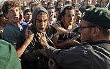 Protesters scuffle with Border Police at the Netiv Ha'Avot outpost in West Bank on June 12, 2018. (Menahem KAHANA/AFP)