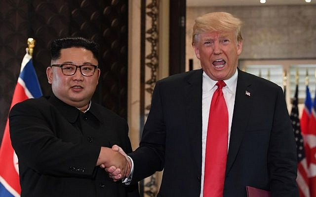 US President Donald Trump (R) and North Korea's leader Kim Jong Un shake hands following a signing ceremony during their historic US-North Korea summit, at the Capella Hotel on Sentosa island in Singapore on June 12, 2018. (AFP PHOTO / SAUL LOEB)