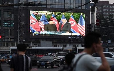 A large screen shows news footage of the summit meeting in Singapore between US President Donald Trump and North Korean leader Kim Jong Un, beside a street in Beijing on June 12, 2018. (AFP PHOTO / GREG BAKER)