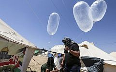 Illustrative. Masked Palestinian men prepare inflated latex condoms loaded with flammable material to be flown towards Israel, at the Israel-Gaza border in al-Bureij, central Gaza Strip on June 14, 2018. (AFP PHOTO / MAHMUD HAMS)