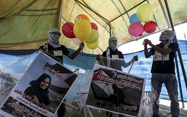Palestinian protesters prepare kites loaded with flammable material to be flown towards Israel, at the Israel-Gaza border in al-Bureij, central Gaza Strip on June 14, 2018. (AFP PHOTO / MAHMUD HAMS)