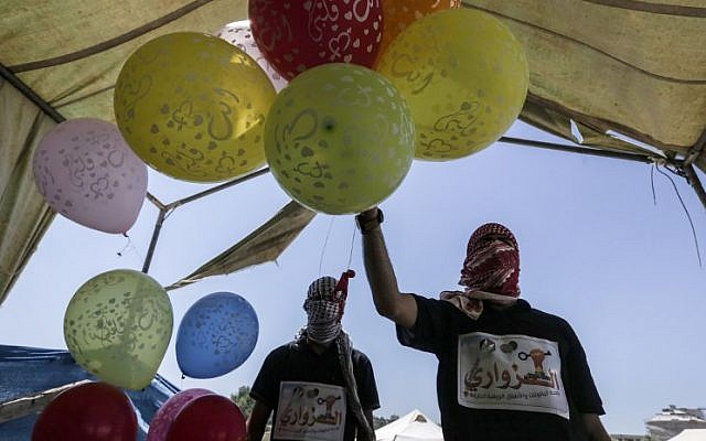Palestinian protesters hold balloons before loading them with flammable material to be flown towards Israel, at the Israel-Gaza border in the central Gaza Strip on June 14, 2018. (AFP/Mahmud Hams)