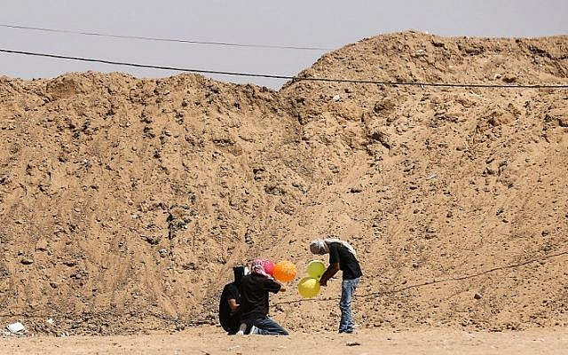 Illustrative: Gazans load balloons with flammable material to be flown toward Israel, at the Israel-Gaza border in al-Bureij, central Gaza Strip on June 14, 2018. (AFP/Mahmud Hams)