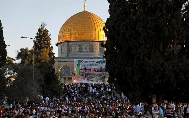 Palestinian Muslims perform the morning Eid al-Fitr prayer near the Dome of Rock at the Al-Aqsa Mosque / Temple Mount compound, Islam's third most holy site, in the Old City of Jerusalem on June 15, 2018. (AFP PHOTO / AHMAD GHARABLI)