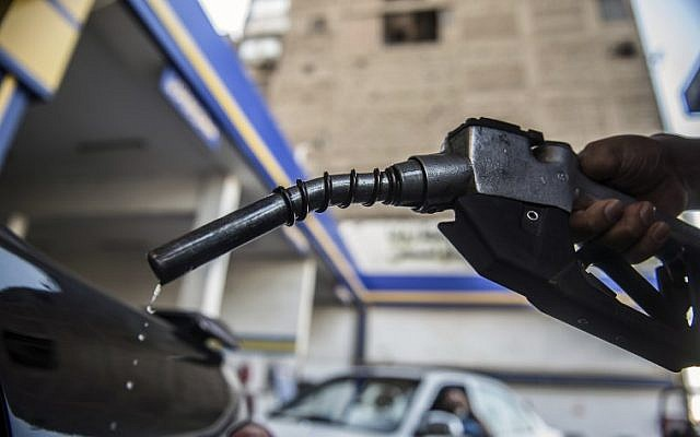 A picture taken on June 29, 2017, in the Egyptian capital Cairo shows fuel dripping from a hose as a gas station worker fills up a customer's tank while cars wait in line. (AFP PHOTO / KHALED DESOUKI)