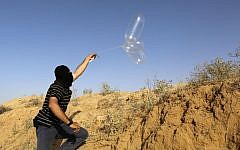 Illustrative: A masked Palestinian man launches a balloon loaded with flammable materials toward Israel from the southern Gaza town of Rafah on June 17, 2018. (AFP Photo/Said Khatib)