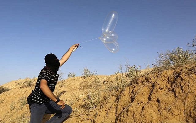 A masked Palestinian man launches a balloon loaded with flammable materials toward Israel from the southern Gaza town of Rafah on June 17, 2018. (AFP Photo/Said Khatib)