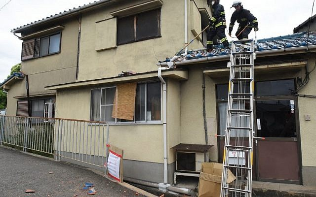 Firefighters check a house damaged by an earthquake in Ibaraki City, north of Osaka prefecture on June 18, 2018. (AFP PHOTO / JIJI PRESS / STR)